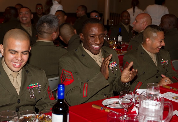 "(From left to right) Sgts. Magno A. Choez, Malik S. King and Ivan A. Livia, quality control clerk, supply clerk and administrative clerk with the 1st Marine Corps District, laugh  as they listen to the commanding officer's decision to fine a Marine during 1 MCD's Mess Night Sept. 7.  Mess night is a Marine Corps tradition passed down by the British Royal Marines with roots that go as far back as the time of the Vikings who held formal dinners to honor battles.  Today's mess nights follow strict rules of conduct, which include games where any member of the mess may accuse another member of a ""crime"" which would require them to pay a fine or drink from the grog, a liquid concoction intended to be distasteful."