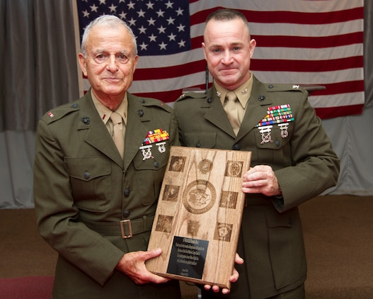 Retired Chief Warrant Officer 4 Ed Farah and Col. J. J. Dill, the commanding officer of the 1st Marine Corps District, show off the plaque presented to Farah at the conclusion of the 1 MCD's Mess Night Sept. 7.  Farah was the guest of honor at the mess night and served in the Marine Corps from 1942 to 1983.  He was present at the Japanese surrender during World War II and also served in the Korean War.