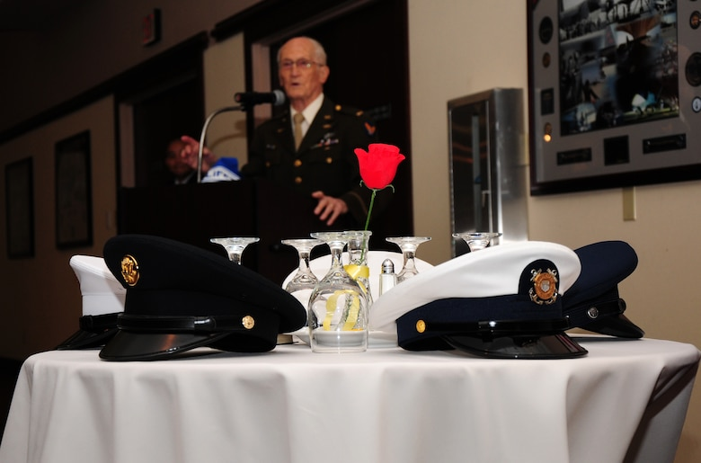Service caps from all branches of the military rest on the POW/MIA table as Leonard Kovar speaks about being a POW in WWII during a Recognition Day Breakfast at the Recce Point Club, Beale Air Force Base, Calif., Sept. 21, 2012. The event was organized by Air Force Sergeants Association Chapter 1372. (U.S. Air Force photo by Senior Airman Allen Pollard/Released)