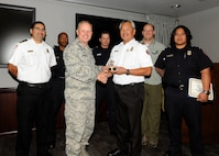 Col. Chris Crawford, 21st Space Wing commander, presents the Gold Knight award to the Waldo Canyon fire initial attack crew from the 721st Civil Engineer Squadron Sept. 19 in the wing conference room. The team consisted of Chris Soliz, Jesse Feldhauser, Brian Zimmerman, Elias Kunishige, Daryl Bolton, Richard Burgess and Tyler Nielsen. (U.S. Air Force photo/Rob Bussard)