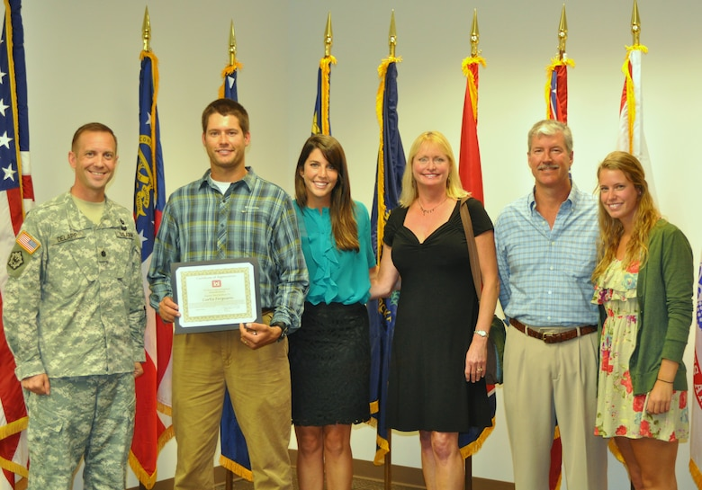 Lt. Col. James A. DeLapp, Nashville District commander, honors Curtis Ferguson, civilian, with a certificate of appreciation and a gold commander's medallion at the Estes Kefauver Federal Building Sept. 17, 2012.  Ferguson heroically pulled two people from the hazardous waters directly downstream of Center Hill Dam after their boat swamped and capsized by the strong current generated by the sluice gates Aug. 16, 2012.  Ferguson was joined (left to right) by his wife Meagan Ferguson, Tricia Ferguson, mother, Scott Ferguson, father, and Casey Ferguson, sister. (USACE photo by Amy Redmond)