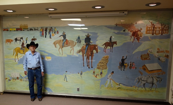 Monroe Moore poses with the mural he painted in 1968 in the Eufaula Powerhouse lobby.
