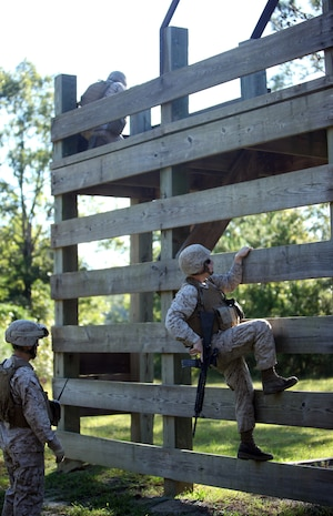 Lance Cpl. Kaley Mitchell, a bulk fuel specialist with 8th Engineer Support Battalion, 2nd Marine Logistics Group, climbs over an obstacle during movement-to-contact training aboard Marine Corps Base Camp Lejeune, N.C., Sept. 25. The purpose of the training was to promote teamwork and combat marksmanship.