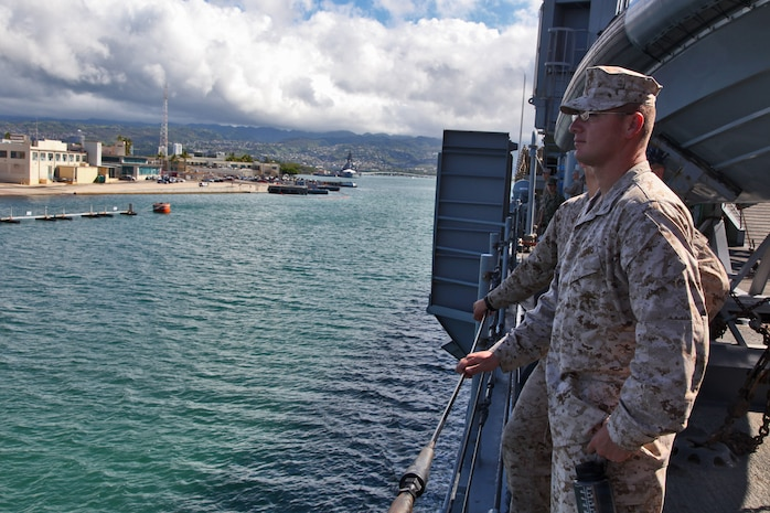 Marines from the 15th Marine Expeditionary Unit watch as the USS Rushmore leaves U.S. Naval Base Pearl Harbor, Hawaii, a week into the unit?s Western Pacific Deployment, Sept. 25. The MEU and Peleliu Amphibious Ready Group will continue their deployment, where they plan to conduct theater security cooperation exercises and humanitarian operations.