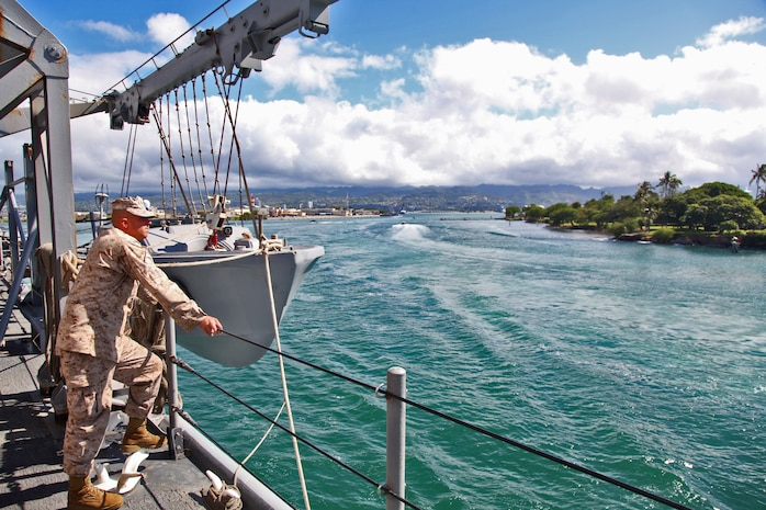 A Marine from the 15th Marine Expeditionary Unit watches as the USS Rushmore leaves U.S. Naval Base Pearl Harbor, Hawaii, a week into the unit?s Western Pacific Deployment, Sept. 25. The MEU and Peleliu Amphibious Ready Group will continue their deployment, where they plan to conduct theater security cooperation exercises and humanitarian operations.::r::::n::::r::::n::