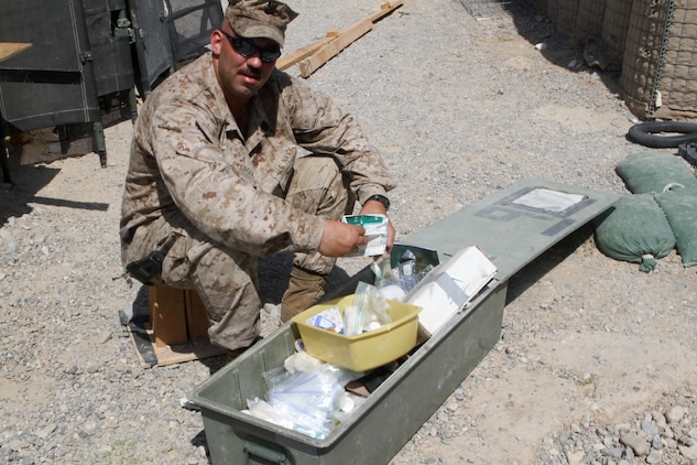 Petty Officer 2nd Class David Cergol, a corpsman with the battalion aid station, 2nd Battalion, 7th Marine Regiment, organizes a box of medical supplies, Sept. 25. Cergol spent his first enlistment as a Seabee and deployed during the initial push into Iraq.