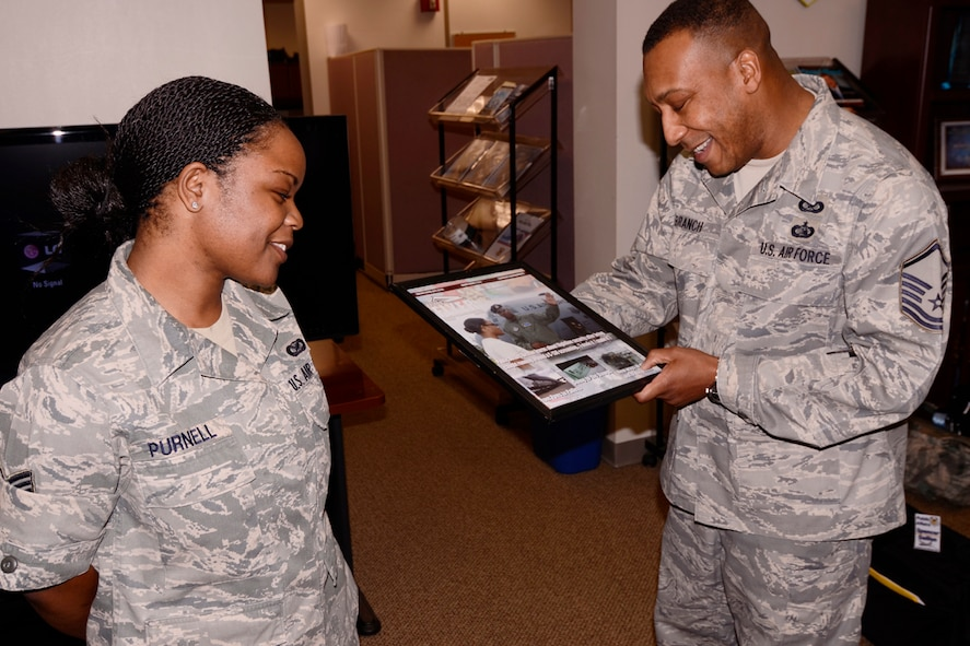 Master Sgt. James Branch, 94th Airlift Wing Public Affairs superintendent, presents Senior Airman Danielle Purnell a certificate of appreciation for her dedication and service to the 94th AW Public Affairs office April 8. Purnell was nominated and to attend Officer Training School and earn a commission through the Deserving Airman Commissioning program. (U.S. Air Force photo/Brad Fallin)