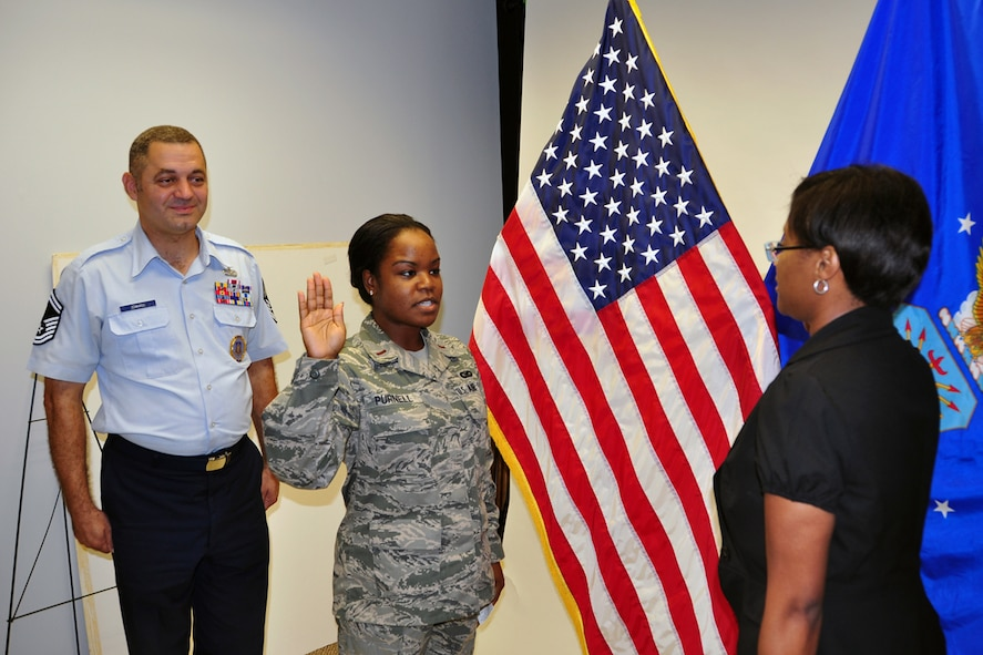 Senior Master Sgt. Michael Edwards, Officer Accession Flight trainer, observes as 2nd Lt. Danielle Purnell leads 2nd Lt. Shannell Emery in the U.S. Air Force Oath of Officer Aug 24. Emery will join the 94th Aeromedical Staging Squadron at Dobbins Air Reserve Base, Ga. (U.S. Air Force photo/Senior Airman Elizabeth Van Patten)