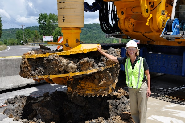 U.S. Army Corps of Engineers Nashville District project manager Linda Adcock stands by a Bauer Foundation Corporation drill rig July 11, 2012 that made the first excavation in the earthen portion of Center Hill Dam to install a concrete barrier wall which is the main feature of the Dam Seepage Rehabilitation project. (USACE photo by Fred Tucker)