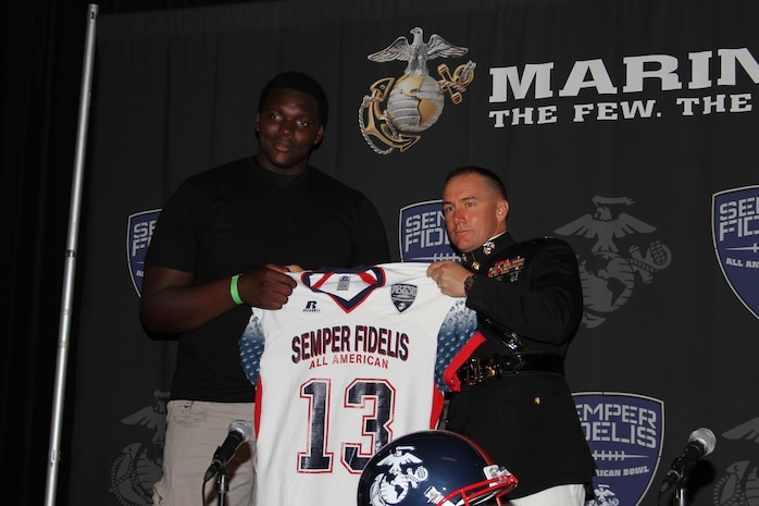 Major Matthew P. Zummo, commanding officer, Recruiting Station Orange County, Calif., presents Aaron Cochran, an offensive lineman from Atwater, Calif., with his 2013 Semper Fidelis All-American Bowl game jersey at the Home Depot Center, Sept. 22. In addition to his success on the football field, Cochran has performed exceptionally well in the classroom, boasting a 3.8 grade point average.