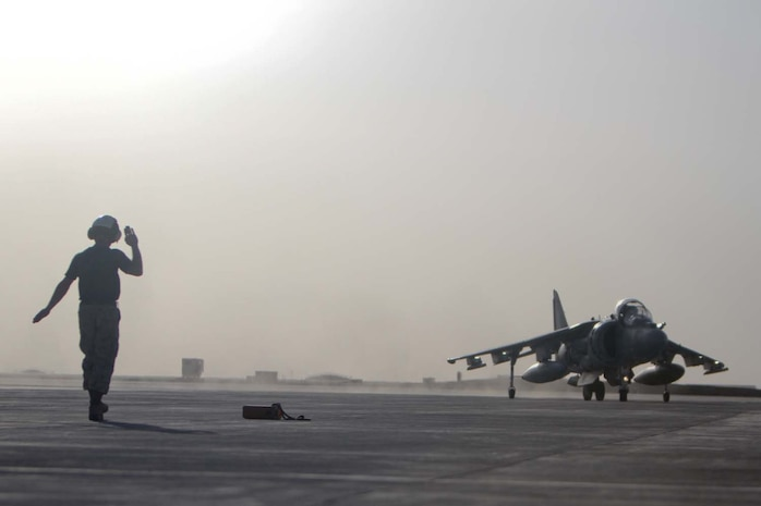 A Marine signals the pilot of an AV-8B Harrier II Plus with Marine Attack Squadron 211, 3rd Marine Aircraft Wing (Forward), into position on the tarmac, Sept. 18, 2012. The Harrier's equipped with a 25 mm Gatling gun and 500-pound bombs.