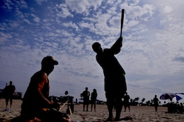 A pitcher and batter assist each other during their turn up to bat during Camp Pendleton's Over-the-Line tournament at the Del Mar Beach, Sept. 22. The tournament served as a pilot event to potentially