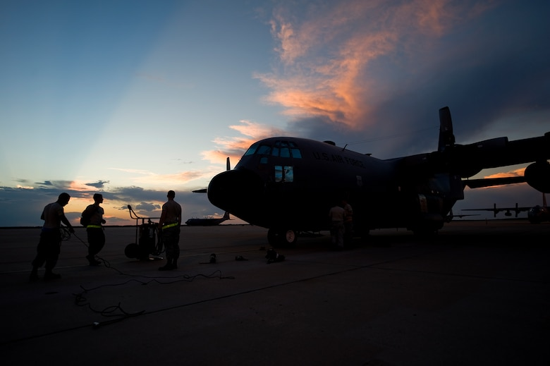 Members of the 317th Airlift Group gather up equipment Sept. 25, 2012, as the sun sets behind one of the last two C-130 Hercules at Dyess Air Force Base, Texas. For 37 years Dyess' C-130 Hercules and its Airmen have built a legacy in the Air Force. That legacy came to end Sept. 26 as the last two C-130 H models, tail numbers 1667 and 2063, departed for Little Rock AFB, Ark. (U.S. Air Force photo by Airman 1st Class Damon Kasberg/ Released)