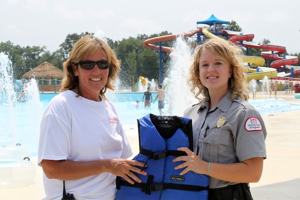 Tammy Wilburn, aquatics supervisor at Somersplash, and Park Ranger Ashley Glyn-Jones at Lake Cumberland, show off one of the many life jackets Somersplash provides for its visitors. (USACE photo by Park Ranger Aurora Scott)