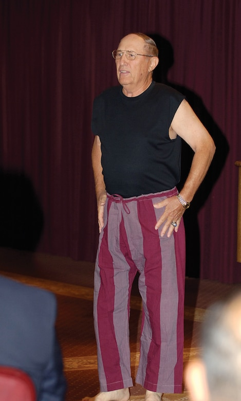 Retired Air Force aviator Col. Leroy Stutz began his talk at Tinker's annual POW/MIA recognition breakfast by peeling off his flight suit to reveal the actual pants he was forced to wear during more than six years of captivity in Vietnam.  (Air Force photo by Margo Wright)