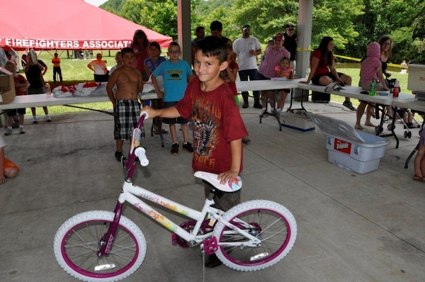 Evan Sproat, 9, proudly displays the bike he won in a drawing at the Cheatham Lake Fish Bustin' Rodeo June 9, 2012 — after being assured that the generous sporting goods store that donated the bike would let him exchange it for another color. (USACE photo by Fred Tucker)