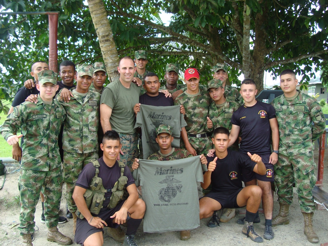 Maj McCormack, a Lat Am FAO conducting a utilization tour in Colombia, visits a riverine post and presents USMC shirts and hats to the winners of a PT competition