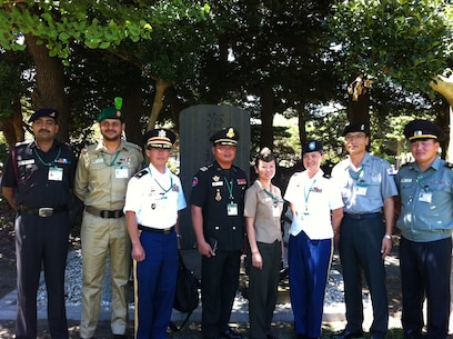 """Maj Coleman with a cohort of International Officers from her Japanese Command & Staff College class, standing at the Japanese Southern Defense Force Communication School; the site where Commodore Perry landed in 1853, """"opening up"""" Japan to the outside world."""