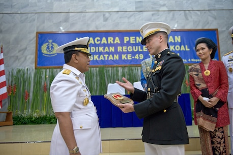 Marine FAO, Major Carpenter, presents a commemorative plaque to Admiral Soeparno, Chief of Staff of the Indonesian Navy, during the graduation ceremony for the Indonesia's Naval Command and Staff College, Class of 2011. Major Carpenter is the first U.S. Marine officer to attend the course, and graduated as the Number One foreign officer in his year group.