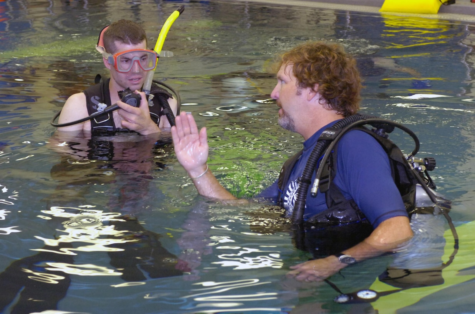 "Wisconsin Army National Guard Sgt. Darrell ""J.R."" Salzman, 27, an Infantryman who lost part of his right arm after the detonation of an explosive device near Baghdad, Iraq, on Dec. 19, 2006, learns to scuba dive from volunteer instructor John W. Thompson, a former National Guardsman, in the Soldiers Undertaking Scuba Diving (SUDS) program at Walter Reed Army Medical Center on June 7, 2007."