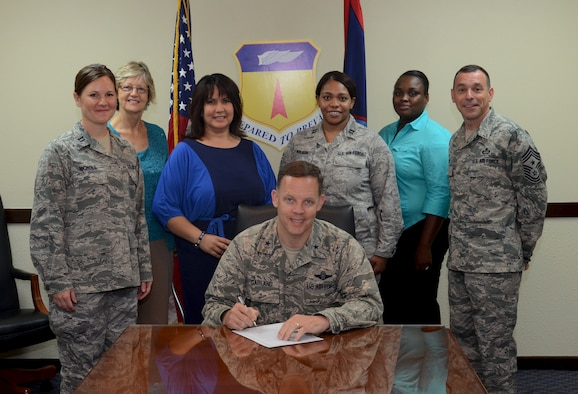 Brig. Gen. Steven Garland signs a proclamation for April's Child Abuse Prevention Month on Andersen Air Force Base, Guam, April 1, 2013. Throughout the month, there are programs and activities scheduled on Andersen AFB that focus on the positive message of supporting children, families and strengthening communities to prevent incidents of child abuse. (U.S. Air Force photo by Senior Airman Benjamin Wiseman/Released)