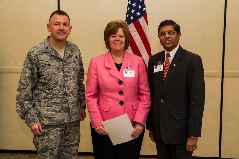 Col. Richard McComb (left), Joint Base Charleston commander, and Jay Patel (right), Advisory Council president present former Honorary Commander  Lisa Mitchell a certificate for her service during the Honorary Commanders Induction Ceremony March 28, 2013, at Joint Base Charleston - Air Base, S.C. The Honorary Commanders program educates local community leaders about the various missions at JB Charleston. (U.S. Air Force photo/ Senior Airman George Goslin)