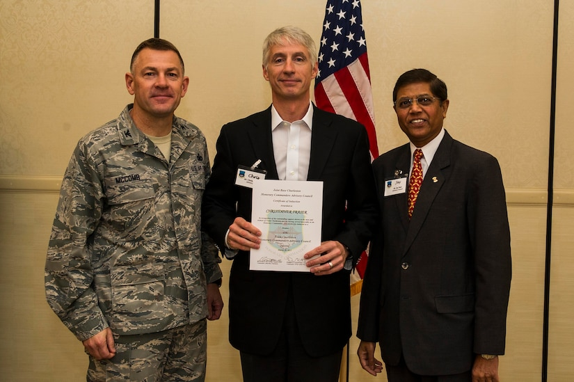 Col. Richard McComb (left), Joint Base Charleston commander, and Jay Patel (right), Advisory Council president, present former Honorary Commander Chris Fraser a certificate for his service during the Honorary Commanders Induction Ceremony March 28, 2013, at Joint Base Charleston - Air Base, S.C. The Honorary Commanders program educates local community leaders about the various missions at JB Charleston. (U.S. Air Force photo/ Senior Airman George Goslin)