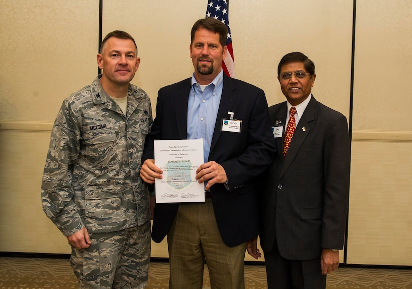 Col. Richard McComb (left), Joint Base Charleston commander, and Jay Patel (right), Advisory Council president, present former Honorary Commander Rob Fifield a certificate for his service during the Honorary Commanders Induction Ceremony March 28, 2013, at Joint Base Charleston - Air Base, S.C. The Honorary Commanders program educates local community leaders about the various missions at JB Charleston. (U.S. Air Force photo/ Senior Airman George Goslin)