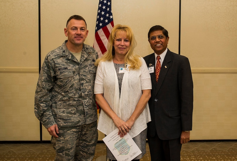 Col. Richard McComb (left), Joint Base Charleston commander, and Jay Patel (right), Advisory Council president, present former Honorary Commander Linda Carrow a certificate for her service during the Honorary Commanders Induction Ceremony March 28, 2013, at Joint Base Charleston - Air Base, S.C. The Honorary Commanders program educates local community leaders about the various missions at JB Charleston. (U.S. Air Force photo/ Senior Airman George Goslin)