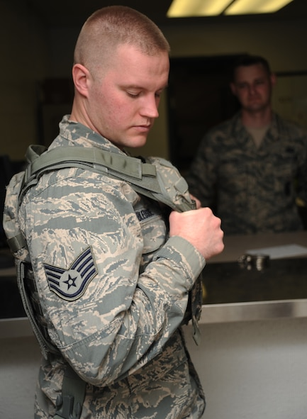 Staff Sgt. Travis Bledsoe, 509th Security Forces Squadron patrolman, tries on a new plate carrier as Tech. Sgt. Jeremy Sanford, 509th SFS NCOIC of supply, oversees, at Whiteman Air Force Base, Mo., March 20, 2013. Sanford issues 20 to 25 pieces of equipment to each new member that arrives to the squadron. (U.S. Air Force photo by Staff Sgt. Nick Wilson/Released)