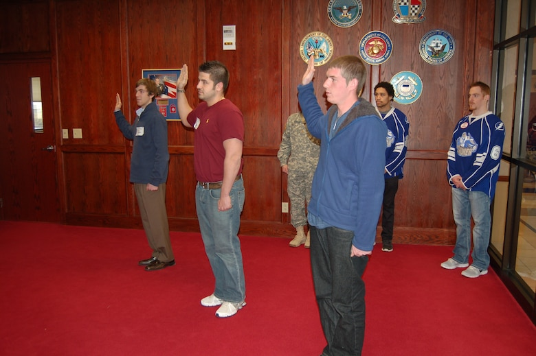 Syracuse Crunch professional hockey players J.T. Brown and Matt Taomina (behind right) observe enlistment oath ceremony at Syracuse Military Entrance Processing Station (MEPS) located on Hancock Field Air National Guard Base, Syracuse, New York.  The Syracuse MEPS is responsible for processing all applicants for enlistment into the Armed Forces between Buffalo and Albany.  It is one of a network of 65 MEPS located across the country. (Photo by Paul J. Salvatore/Released).
