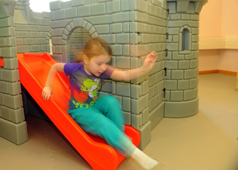 SPANGDAHLEM AIR BASE, Germany -- Allison Aiken, daughter of U.S. Air Force Master Sgt. Patrick Aiken, 52nd Component Maintenance Squadron, slides down from a children's castle April 2, 2013, after the opening ceremony for Spangdahlem Air Base's new child playroom. The 52nd Civil Engineer Squadron renovated the room, and the funds for the play items came from the Spangdahlem Spouses and Enlisted Members Club; Officers and Civilian Spouses Club; and the Bitburg Middle School Parent Teacher Student Association. (U.S. Air Force photo by Staff Sgt. Daryl Knee/Released)