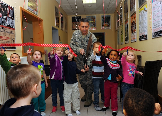 SPANGDAHLEM AIR BASE, Germany -- U.S. Air Force Col. David Julazadeh, 52nd Fighter Wing commander from Chillacothe, Ill., cuts a ribbon April 2, 2013, at the opening ceremony for Spangdahlem Air Base's new child playroom. Children helped Julazadeh cut the ribbon before entering the playroom for first-hand testing. The $4,000 project includes the renovation to the room, a seating area for parents and numerous playroom items. (U.S. Air Force photo by Staff Sgt. Daryl Knee/Released)