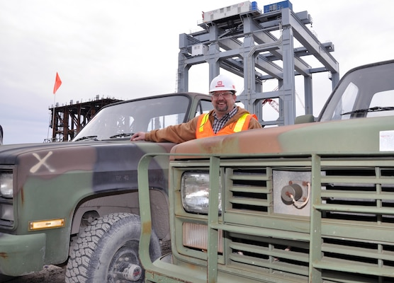 With a dam shell lifting frame and the super gantry crane in the background, Hawley stands between two of the 10 5/4-ton Chevy pickups he has acquired through GSAXcess and saved the Olmsted Locks and Dam construction project, Olmsted, Ill., tens of thousands of dollars. (U.S. Army Corps of Engineers photo by Jon Fleshman)