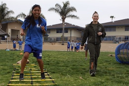 Samatha Luna, left, navigates through the agility portion of an obstacle course as Cpl. Jaclyn L. Mickelson, guides her during the Marine Corps Physical Education Fitness Challenge at JMS here, March 29. Luna is a 13-year-old eighth-grade student at Jefferson Middle School and Mickelson is an administrative clerk with Camp Pendleton's Security Battalion here.
