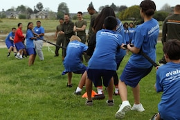 Students participate in a tug-of-war competition during the Marine Corps Physical Education Fitness Challenge at Jefferson Middle School here, March 29. During each physical education class, hundreds of students gathered at the school's track and football field where Marine volunteers from Pendleton's Single Marine Program held the four-station obstacle course.