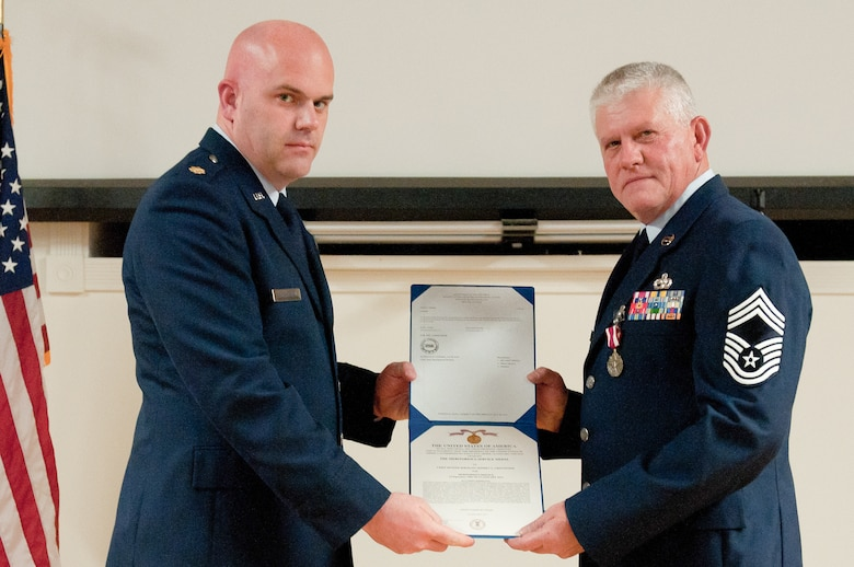Chief Master Sgt. Jeffrey L. Greenwood (right) is presented with a Meritorious Service Medal by Maj. Kevin E. Thornberry, commander of the 123rd Logistics Readiness Squadron, during a retirement ceremony held in Greenwood's honor at the Kentucky Air National Guard Base in Louisville, Ky., on Jan. 13, 2013. Greenwood, the 123rd Airlift Wing's vehicle fleet manager, served in the active-duty Air Force and Air National Guard for 32 years. (U.S. Air Force photo illustration by Airman Joshua Horton)