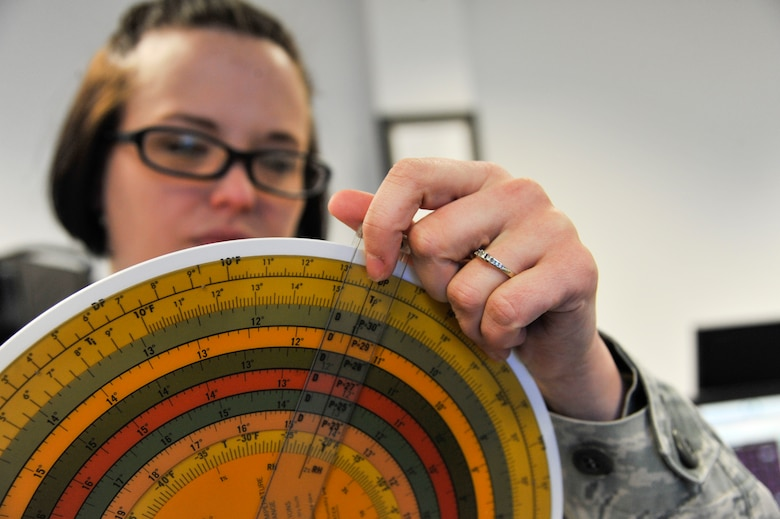 U.S. Air Force Senior Airman Heather Rieck, 509th Operation Support Squadron weather journeyman, examines a slide rule, Whiteman Air Force Base, Mo., March 20, 2013. Before the extensive use of computers, a slide ruler was used to calculate temperature, dew point, atmospheric pressure and wind speeds. (U.S. Air Force photo by Airman 1st Class Keenan Berry/Released)