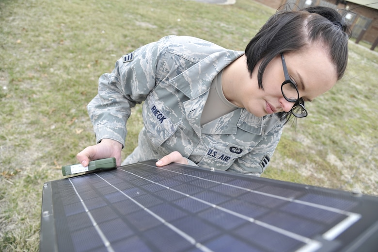U.S. Air Force Senior Airman Heather Rieck, 509th Operation Support Squadron weather journeyman, adjusts a solar panel on a TMQ-53, Whiteman Air Force Base, Mo., March 20, 2013. The solar panel is aimed toward the sun to draw the most energy, providing power to equipment on the censor. (U.S. Air Force photo by Airman 1st Class Keenan Berry/Released)