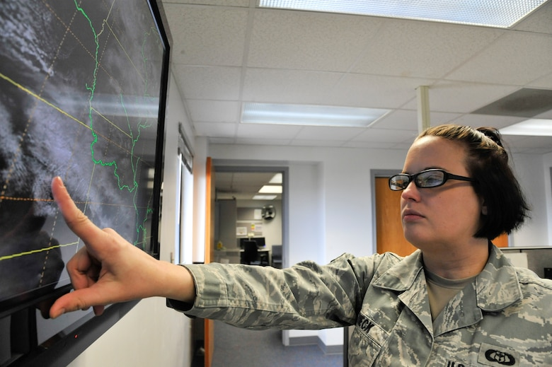 U.S. Air Force Senior Airman Heather Rieck, 509th Operation Support Squadron weather journeyman, looks at satellite pictures, Whiteman Air Force Base, Mo., March 20, 2013. Satellites send pictures from outer space to provide weather personnel with information about cloud cover and potential weather hazards that may affect the base. (U.S. Air Force photo by Airman 1st Class Keenan Berry/Released)