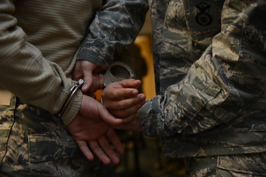 SPANGDAHLEM AIR BASE, Germany – U.S. Air Force Senior Airman Andrew Lehman, 52nd Security Forces Squadron security forces member from San Angelo, Texas, handcuffs U.S. Air Force Airman 1st Class Anthony Santiago, 52nd SFS security forces member from New Port Richey, Fla., during a training exercise April 2, 2013. Security forces members train continually to keep their apprehension abilities proficient in case of real-world situations. (U.S. Air Force photo by Airman 1st Class Gustavo Castillo/Released)