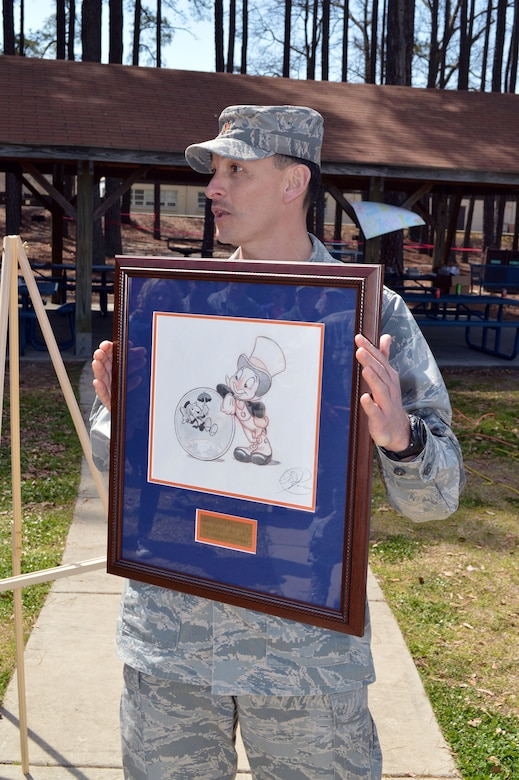 Maj. Joseph Whittington, 3rd Aerial Port Squadron commander, unveils an original Disney caricature drawing of the squadron's mascot, Jiminy Cricket, during a picnic March 29, celebrating the squadron's 60th Anniversary at Pope Army Airfield, Fort Bragg, N.C.