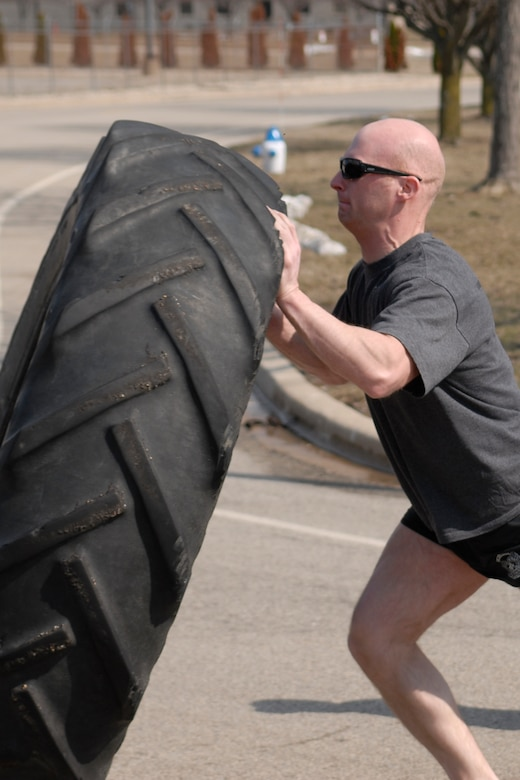 U.S. Air Force Staff Sgt. and Tactical Air Control Party specialist Nathan Adams flips a 230 pound tractor tire across the final lap of the TACP Association 24 Hour Run Challenge at the 182nd Airlift Wing in Peoria, Ill., March 29, 2013.  Sixty-two runners ran 161.75 miles around the installation over the course of 24 hours and raised over $8,200 in support of the TACP community and their families.  The 182nd team also ran in remembrance of Staff Sgt. Jacob Frazier, a member of the Peoria-based 169th Air Support Operations Squadron who was killed in action near Geresk, Afghanistan, exactly 10 years earlier.  (U.S. Air Force photo by Staff Sgt. Lealan Buehrer//Released)(This image was cropped to emphasize the subject of the image.)