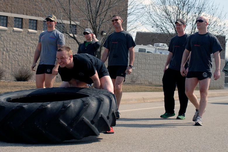 U.S. Air Force Senior Airman Nicolas Menz and fellow Tactical Air Control Party specialists flip a 230 pound tractor tire across the final lap of the TACP Association 24 Hour Run Challenge at the 182nd Airlift Wing in Peoria, Ill., March 29, 2013.  Sixty-two runners ran 161.75 miles around the installation over the course of 24 hours and raised over $8,200 in support of the TACP community and their families.  The 182nd team also ran in remembrance of Staff Sgt. Jacob Frazier, a member of the Peoria-based 169th Air Support Operations Squadron who was killed in action near Geresk, Afghanistan, exactly 10 years earlier.  (U.S. Air Force photo by Staff Sgt. Lealan Buehrer//Released)