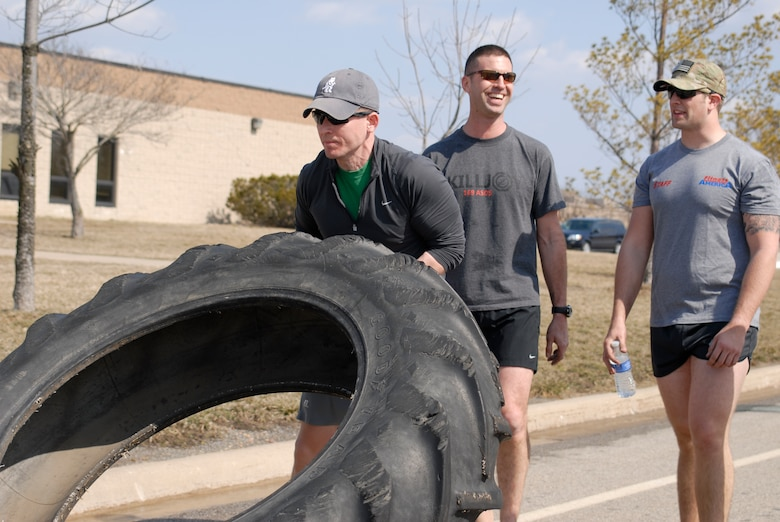 U.S. Air Force Capt. Daniel Curtin and fellow Tactical Air Control Party specialists flip a 230 pound tractor tire across the final lap of the TACP Association 24 Hour Run Challenge at the 182nd Airlift Wing in Peoria, Ill., March 29, 2013.  Sixty-two runners ran 161.75 miles around the installation over the course of 24 hours and raised over $8,200 in support of the TACP community and their families.  The 182nd team also ran in remembrance of Staff Sgt. Jacob Frazier, a member of the Peoria-based 169th Air Support Operations Squadron who was killed in action near Geresk, Afghanistan, exactly 10 years earlier.  (U.S. Air Force photo by Staff Sgt. Lealan Buehrer//Released)