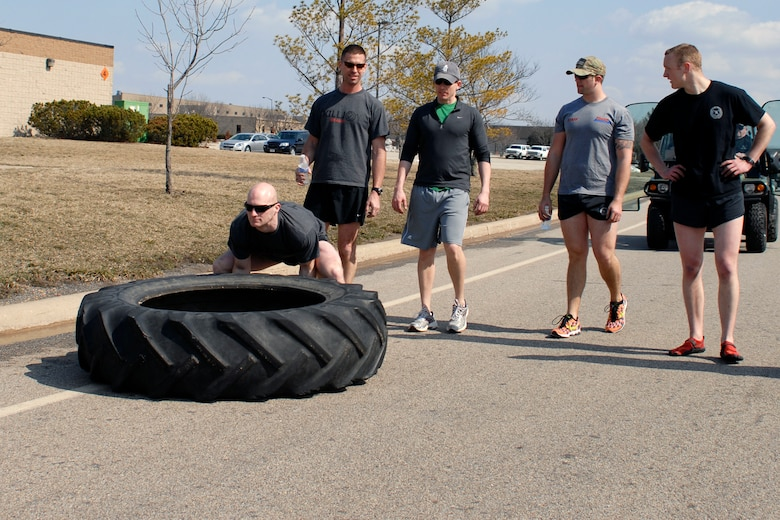 U.S. Air Force Staff Sgt. Nathan Adams and fellow Tactical Air Control Party specialists flip a 230 pound tractor tire across the final lap of the TACP Association 24 Hour Run Challenge at the 182nd Airlift Wing in Peoria, Ill., March 29, 2013.  Sixty-two runners ran 161.75 miles around the installation over the course of 24 hours and raised over $8,200 in support of the TACP community and their families.  The 182nd team also ran in remembrance of Staff Sgt. Jacob Frazier, a member of the Peoria-based 169th Air Support Operations Squadron who was killed in action near Geresk, Afghanistan, exactly 10 years earlier.  (U.S. Air Force photo by Staff Sgt. Lealan Buehrer//Released)(This image was cropped to emphasize the subject of the image.)