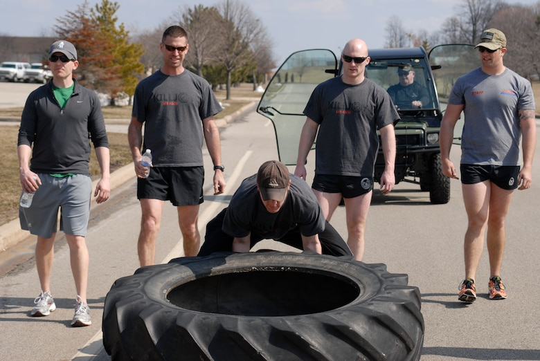 U.S. Air Force Senior Airman Cody Canfield and fellow Tactical Air Control Party specialists flip a 230 pound tractor tire across the final lap of the TACP Association 24 Hour Run Challenge at the 182nd Airlift Wing in Peoria, Ill., March 29, 2013.  Sixty-two runners ran 161.75 miles around the installation over the course of 24 hours and raised over $8,200 in support of the TACP community and their families.  The 182nd team also ran in remembrance of Staff Sgt. Jacob Frazier, a member of the Peoria-based 169th Air Support Operations Squadron who was killed in action near Geresk, Afghanistan, exactly 10 years earlier.  (U.S. Air Force photo by Staff Sgt. Lealan Buehrer//Released)(This image was cropped to emphasize the subject of the image.)