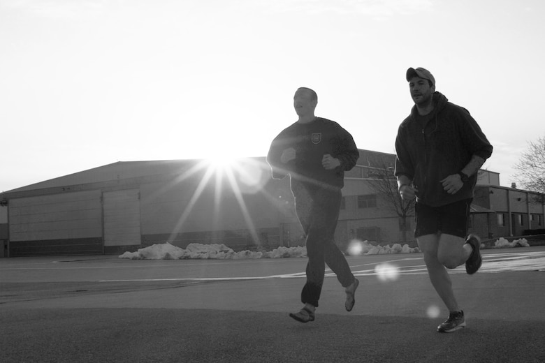 U.S. Air Force Senior Airmen Nicolas Menz, left, and Rob Design run past the sun setting on an aircraft hangar during the second annual Tactical Air Control Party Association 24 Hour Run Challenge at the 182nd Airlift Wing in Peoria, Ill., March 28, 2013.  Sixty-two runners ran 161.75 miles around the installation over the course of 24 hours and raised over $8,200 in support of the TACP community and their families.  The 182nd team also ran in remembrance of Staff Sgt. Jacob Frazier, a member of the Peoria-based 169th Air Support Operations Squadron who was killed in action near Geresk, Afghanistan, 10 years earlier on March 29, 2003.  (U.S. Air Force photo by Staff Sgt. Lealan Buehrer//Released)