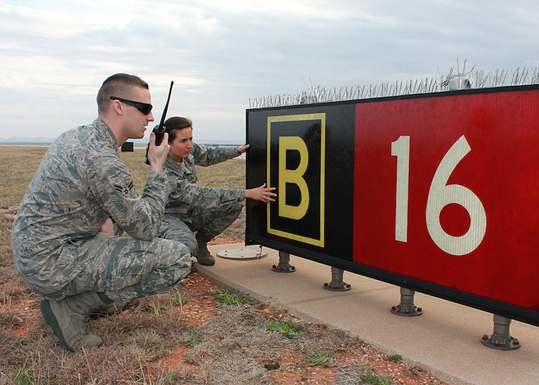Airman 1st Class Laramie Combs and Airman 1st Class Tori Reyes, 7th Operations Support Squadron, notify the Dyess airfield operations counter about airfield signage concerns during a recent air traffic system evaluation at Dyess Air Force Base, Texas. The 7th OSS, Airfield Operations Flight, Airfield Management was recently awarded the Headquarters Air Force Ronald B. McCarty Airfield Management Facility of the Year of 2011. (U.S. Air Force photo by Senior Airman Evan Stewart/Released)