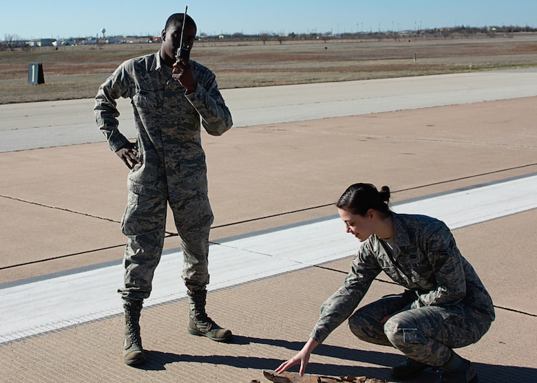 Senior Airman Aaron Henry, left, and Airman 1st Class Gabrielle Aragon, right, 7th Operations Support Squadron, notify Dyess tower about foreign object debris on the runway during a recent air traffic system evaluation at Dyess Air Force Base, Texas. The 7th OSS, Airfield Operations Flight, Airfield Management was recently awarded the Headquarters Air Force Ronald B. McCarty Airfield Management Facility of the Year of 2011. (U.S. Air Force photo by Senior Airman Evan Stewart/Released)